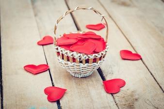 Coração vermelho na cesta na tabela de madeira para o conceito do dia de são valentim e do amor com espaço da cópia.