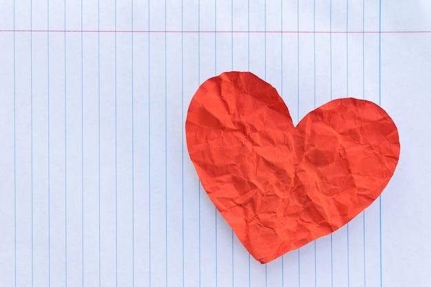 Coração vermelho na folha branca forrada do bloco de notas