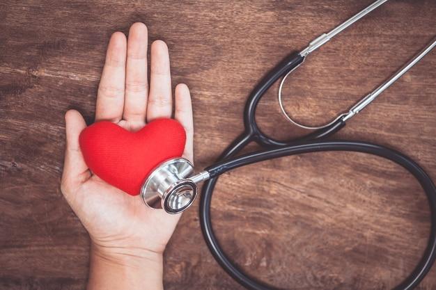 Coração vermelho na mão da mulher com estetoscópio de médico em fundo de madeira. conceito médico de saúde