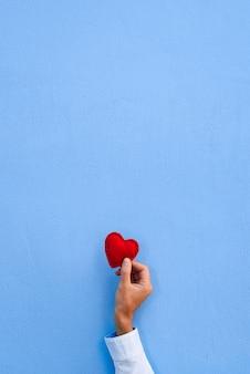 Coração vermelho na mão de um homem no fundo da parede azul. cartão de dia dos namorados
