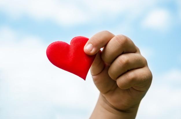 Coração vermelho na mão de uma criança contra o céu