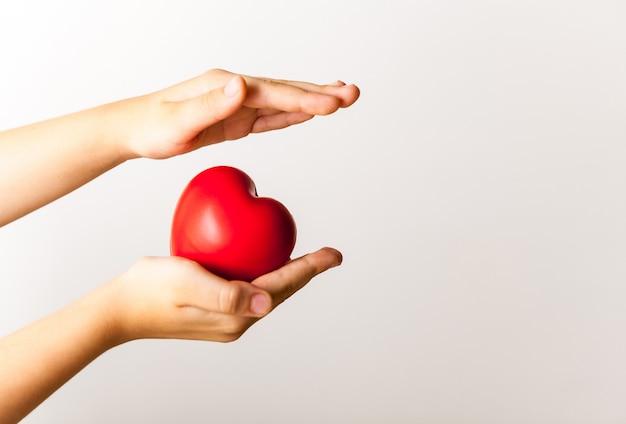 Coração vermelho nas mãos da criança na luz de fundo