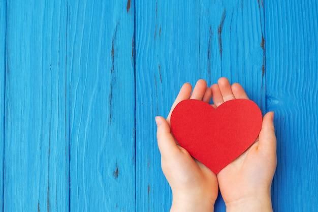 Coração vermelho nas mãos da criança