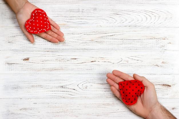 Coração vermelho nas mãos de mulher e homem, no fundo de madeira