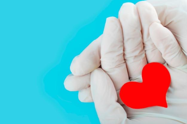 Coração vermelho nas mãos de uma enfermeira. dia mundial do dador de sangue.