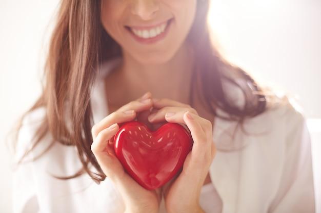 Coração vermelho nas mãos de uma mulher
