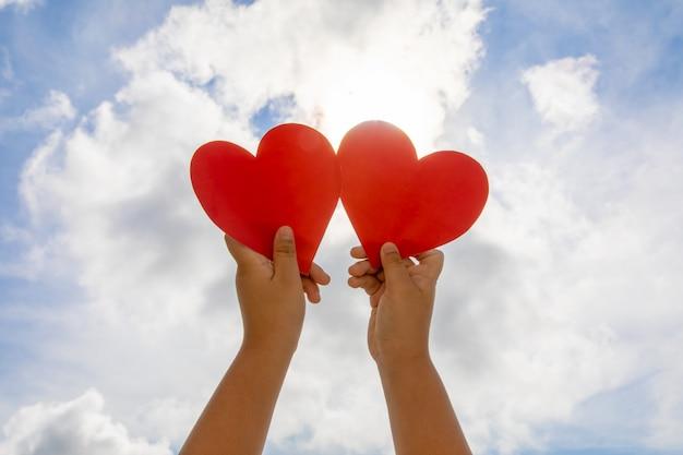 Coração vermelho nas mãos no fundo do céu