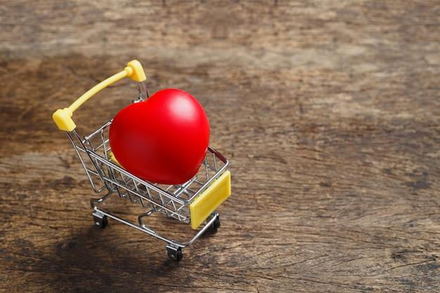 Coração vermelho no carrinho de compras na mesa de madeira. conceito de amor e saúde.
