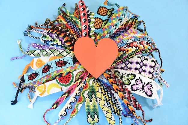 Coração vermelho no meio do círculo de muitas pulseiras de amizade diy
