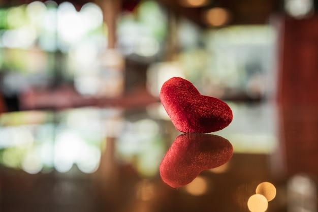 Coração vermelho no vidro com fundo de bokeh de reflexão