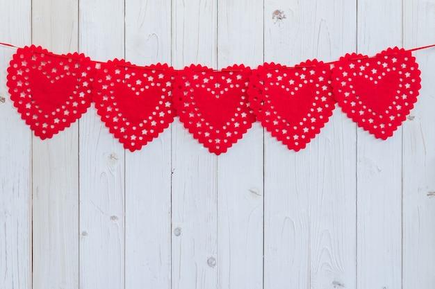 Coração vermelho pendurado em madeira branca para comemoração com espaço.