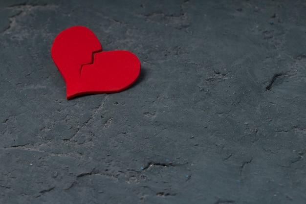 Coração vermelho rachado na parede de concreto