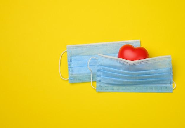 Coração vermelho repousa sobre uma máscara médica descartável branca, fundo amarelo, espaço de cópia