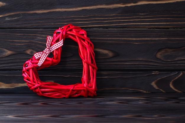 Coração vermelho sobre fundo escuro de madeira. textura de placas marrons. cartão de presente de dia dos namorados. símbolo do amor, conceito romântico. quadro de férias em estilo lacônico, minimalismo.
