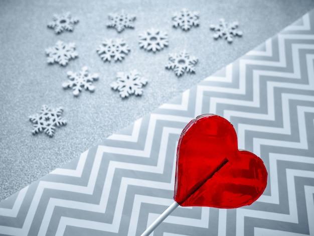 Coração vermelho sobre um fundo desfocado com linhas geométricas e flocos de neve.