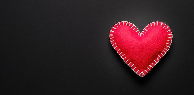 Coração vermelho sobre um fundo preto. conceito de seguro de saúde, dia mundial da saúde, dia mundial da hipertensão, proteção da saúde.