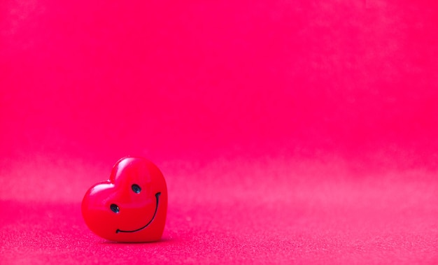 Coração vermelho sobre um fundo rosa brilhante, copie o espaço.