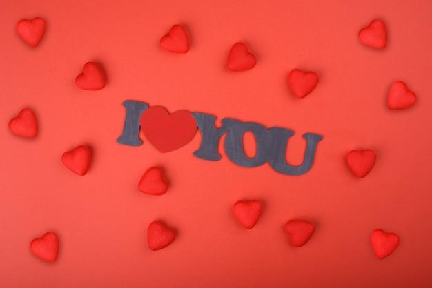 Coração vermelho sobre um fundo vermelho com uma inscrição no centro eu te amo. dia dos namorados
