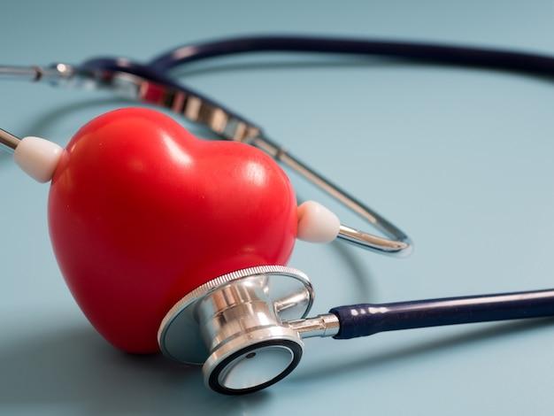 Coração vermelho usando o estetoscópio azul profundo sobre o fundo azul para ouvir seu próprio coração