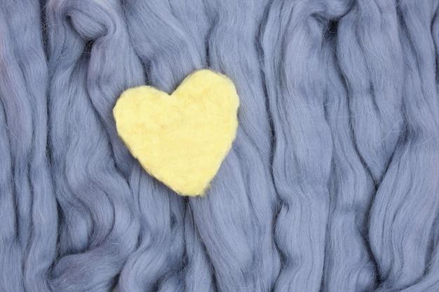 Corações amarelos feitos de lã em uma superfície de lã cinza