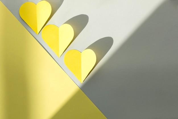 Corações amarelos recortados de papel colorido em um fundo cinza, vista superior, cores 2021. conceito de dia dos namorados colorido na moda.