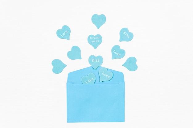Corações azuis com texto amor, beijo, para sempre voam para fora do envelope azul sobre fundo branco.