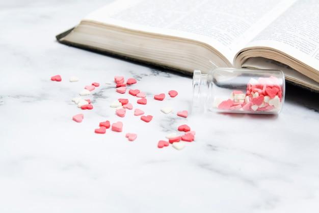 Corações caíram de uma garrafa perto de uma bíblia aberta. bíblia como fonte do conceito de amor