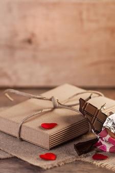 Corações, chocolate e presente do dia dos namorados em fundo de madeira