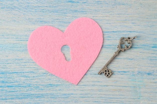 Corações com um buraco de fechadura e uma chave no fundo azul de madeira do dia dos namorados.
