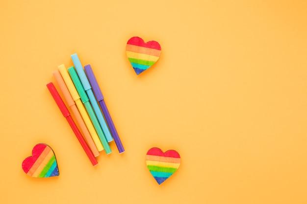 Corações de arco-íris com canetas de feltro na mesa