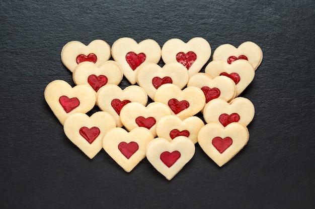 Corações de biscoitos caseiros com geléia de morango na mesa de ardósia