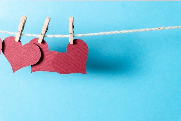 Corações de borgonha que penduram em uma corda com prendedores de roupa minúsculos em um fundo azul.