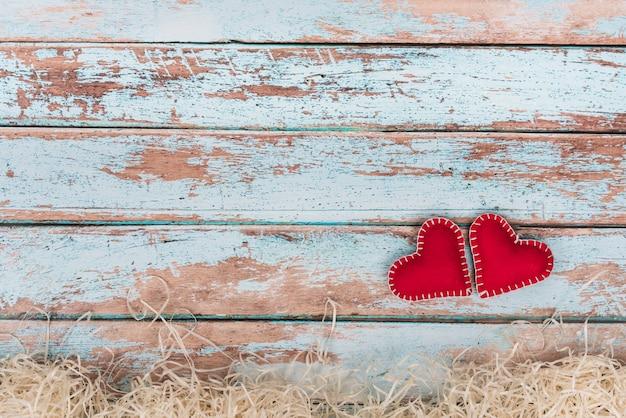 Corações de brinquedo macio na mesa de madeira azul