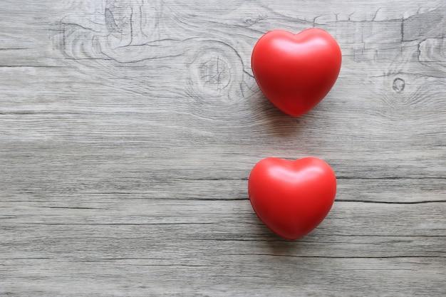 Corações de brinquedo vermelho na mesa de madeira