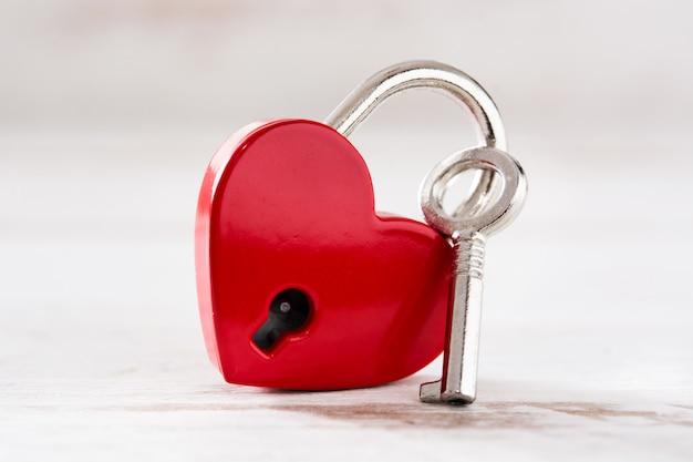 Corações de cadeado vermelho com chave no fundo branco de madeira