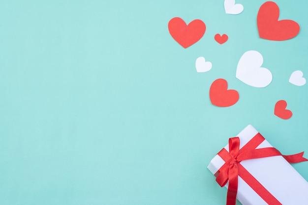 Corações de caixa de presente, vermelho e branco sobre fundo azul pastel. dia dos namorados ou conceito de cerimônia de casamento