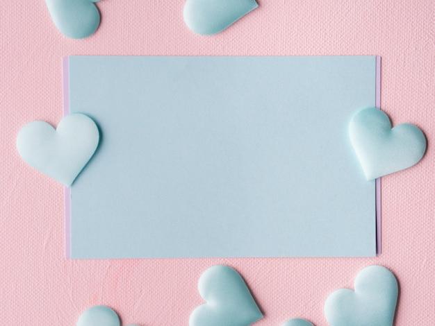 Corações de cartão pastel verde no fundo texturizado rosa