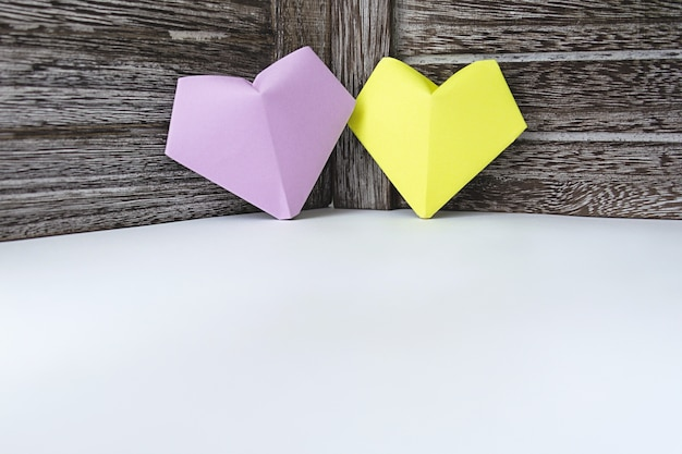 Corações de cor lilás e amarelo de papel estão no fundo de uma placa de madeira escura