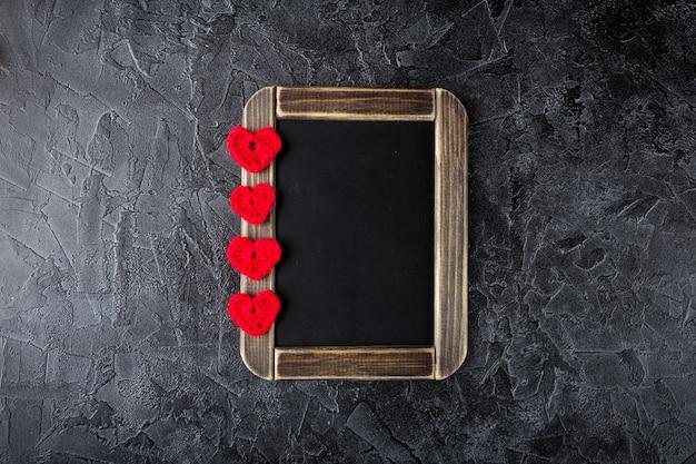 Corações de crochê de malha decorativos e quadro-negro. dia dos namorados. postura plana. vista do topo.