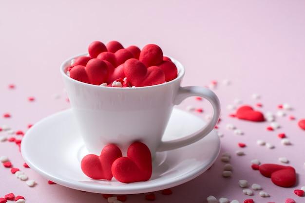 Corações de doces de açúcar doce vermelho em uma xícara de café. conceito de amor e dia dos namorados. fundo festivo