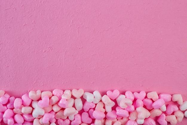Corações de espuma rosa papel rosa fundo