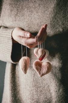 Corações de feltro nas mãos femininas