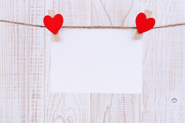 Corações de feltro vermelho artesanal e papel branco pendurado em uma corda com prendedores de roupa