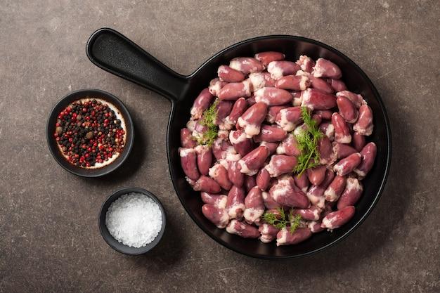 Corações de frango crus na frigideira, sal e pimenta na mesa da cozinha