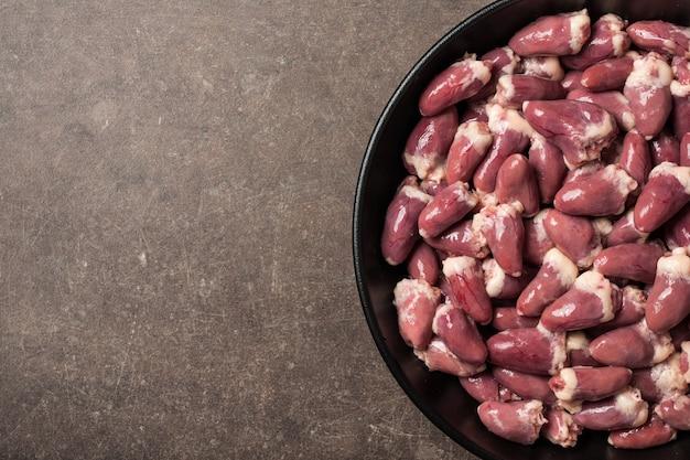 Corações de frango crus na frigideira