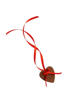 Corações de gengibre festivos no dia dos namorados com fita vermelha isolada no fundo branco.