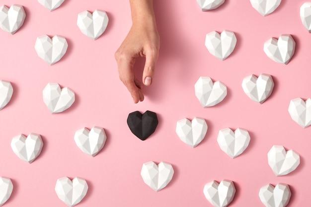 Corações de gesso branco e mão de mulher colocam coração preto