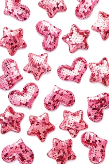 Corações de lantejoulas rosa e estrelas na mesa branca.