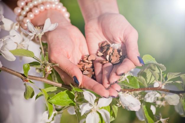 Corações de madeira amam as mãos da mulher atrás da macieira de flor. conceito de paz e harmonia. segurando coração forma símbolo de amor feriado dia dos namorados saudação romântica conceito de sentimentos de estilo de vida