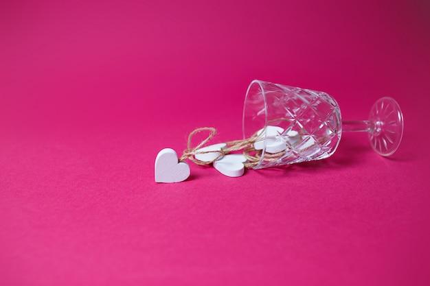 Corações de madeira brancos pequenos no copo de vinho deitado no fundo rosa com espaço de cópia.